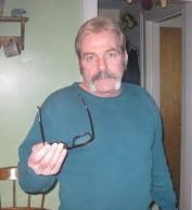 photograph of man with mustache holding out glasses