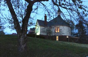 church building at dusk with windows lit, tree in foreground