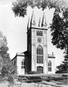 black and white photograph of wooden Gothic church building with tall square tower