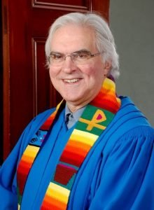 Rev. Mark Harris wearing a blue robe and multicolored stole