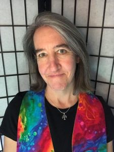 portrait of woman with gray hair wearing rainbow colored stole over black t-shirt